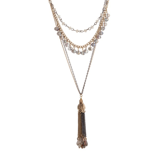 Worn gold tone necklace displaying layers of ivory and gray beads and a two tone chain tassel with ivory beads.