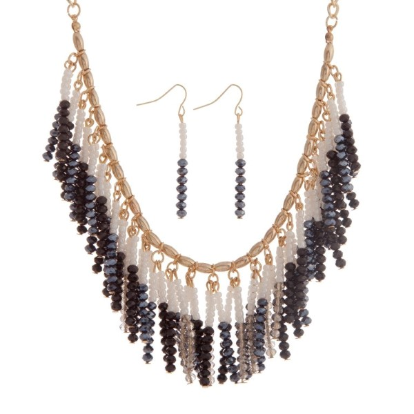 """Gold tone necklace set with a cluster of hanging black, navy, and white beads. Approximately 18"""" in length."""