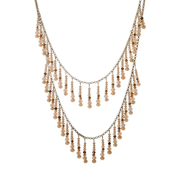 "Burnished gold tone layering necklace with a cluster and beige dangling beads. Approximately 33"" in length."