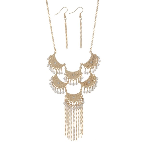"Gold tone necklace set displaying crescents with dangling clear beads and metal fringe. Approximately 15"" in length."