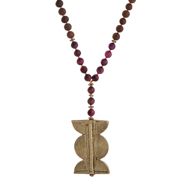 "Burnished gold tone half beaded necklace displaying fuchsia and brown wood beads with a 2 1/2"" gold tone pendant. Approximately 35"" in length. Handmade in the USA."