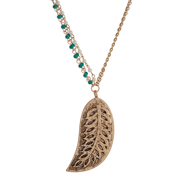 "Worn gold tone necklace displaying turquoise beads and faux pearls with a 3"" leaf pendant. Approximately 31"" in length."