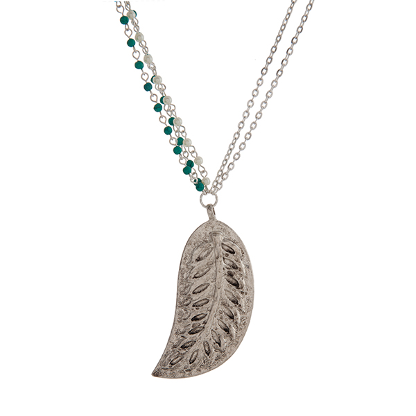 "Worn silver tone necklace displaying turquoise beads and faux pearls with a 3"" leaf pendant. Approximately 31"" in length."