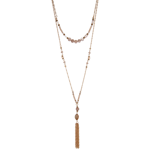"""Gold tone layering necklace displaying ivory beads and a brown stone with a chain tassel. Approximately 28"""" in length."""