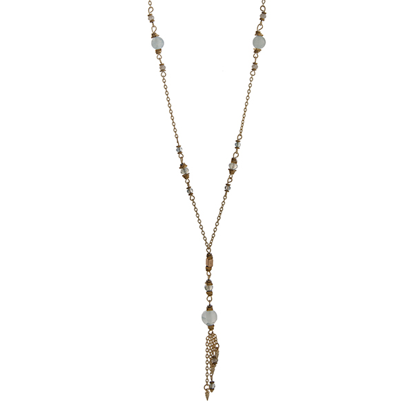 """Gold tone necklace displaying mint bead stations and a tassel with mini spikes. Approximately 30"""" in length."""