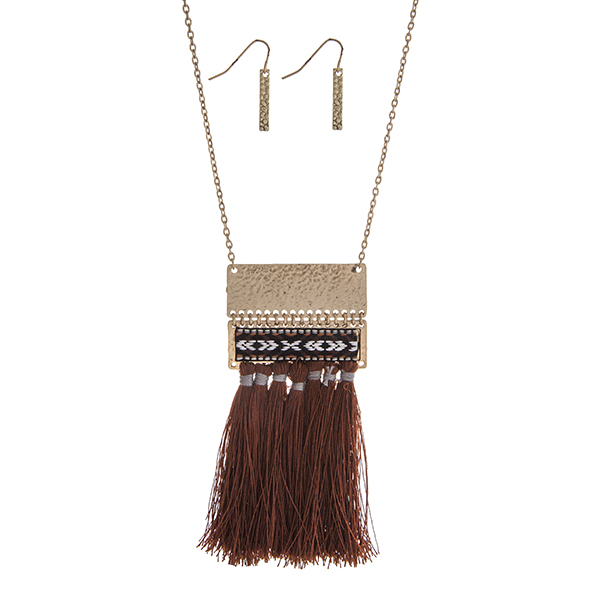 """Gold tone necklace set displaying a hammered pendant with a black, white, and brown tribal print thread and brown tassels. Approximately 28"""" in length."""