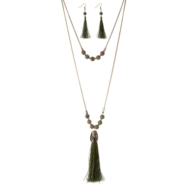 """Gold tone layering necklace set displaying green beads with a 4"""" teal tassel. Approximately 27"""" in length."""