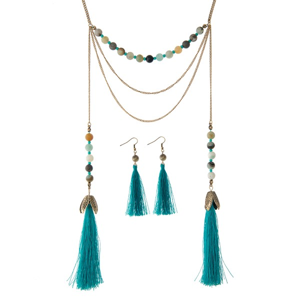 "Gold tone necklace set displaying amazonite beads with two 3 1/2"" teal tassels at the end. Approximately 28"" in length."