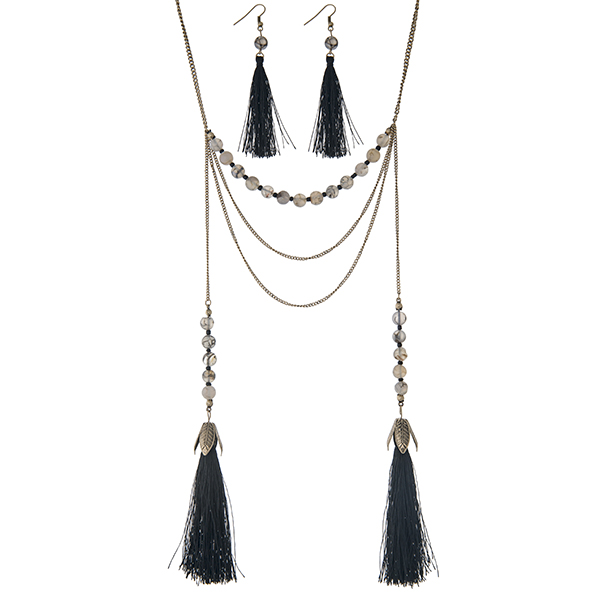 "Burnished gold tone layering necklace set displaying black and white beads with two 3 1/2"" fabric tassels. Approximately 28"" in length."