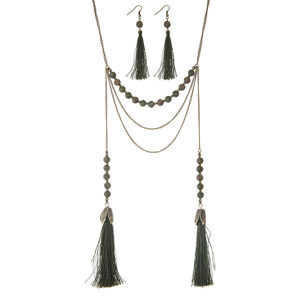 "Burnished gold tone layering necklace set displaying green and brown beads with two 3 1/2"" fabric tassels. Approximately 28"" in length."