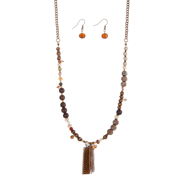 """Burnished gold tone necklace set displaying brown beads, a bar with topaz rhinestones, and a chain tassel. Approximately 28"""" in length."""