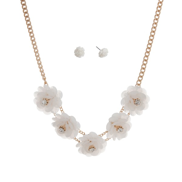 "Gold tone necklace set displaying five white flowers with rhinestone accents. Approximately 17"" in length."