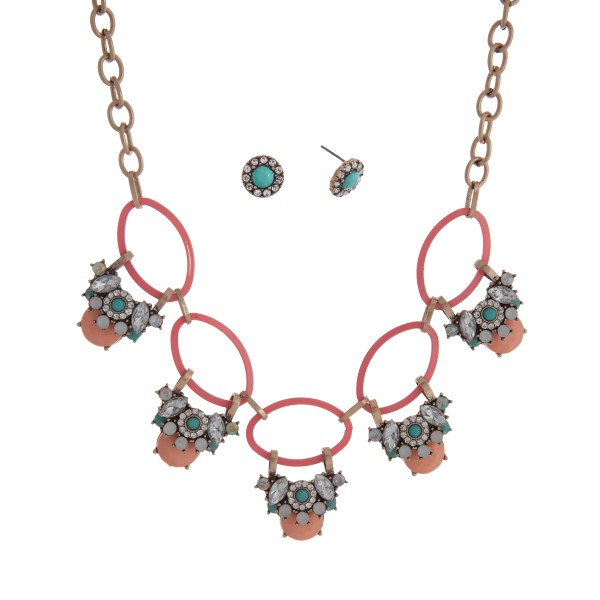 "Gold tone necklace set displaying pink rings with layered peach, mint, and clear cabochons. Approximately 17"" in length."