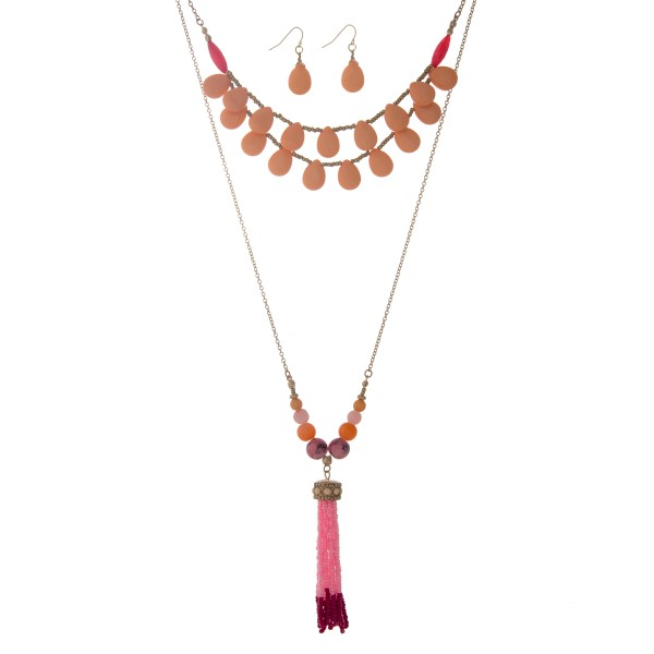 "Gold tone layering necklace set displaying peach teardrop shaped beads and a 3"" pink and fuchsia seed bead tassel. Approximately 32"" in length."