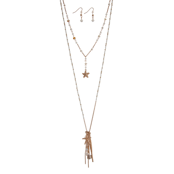 """Gold tone layering necklace set displaying white beads with a starfish  and coral reef charms, hanging chains, and two bars. Approximately 31"""" in length."""