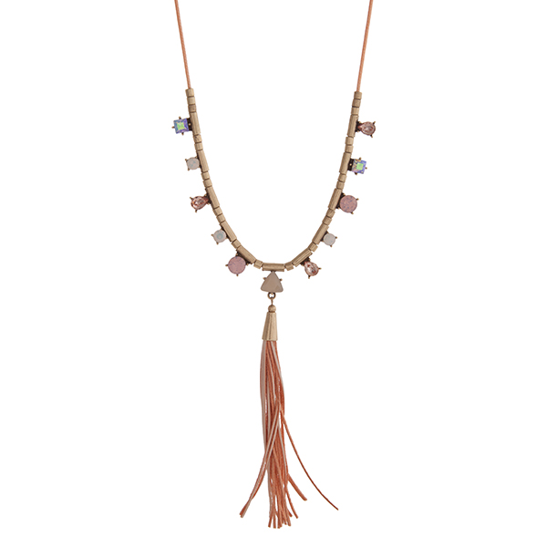 """Peach cord necklace displaying pink, peach, and white cabochons with a peach leather tassel and gold tone accents. Approximately 30"""" in length."""