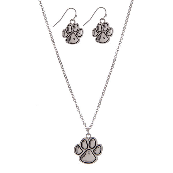"18"" silver tone necklace set displaying a small paw print pendant with the matching earrings."
