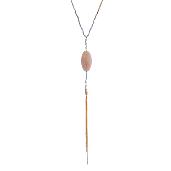 """Gold tone necklace displaying blue beads with an oval white natural stone and chain tassel. Approximately 32"""" in length."""