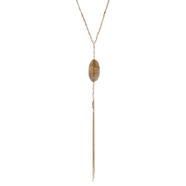 """Gold tone necklace displaying beige beads with an oval natural stone and chain tassel. Approximately 32"""" in length."""