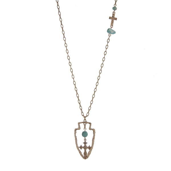 "Burnished gold tone necklace displaying a hammered cross station with a turquoise stone and bead and a wire wrapped arrowhead pendant with a turquoise bead and hanging cross. Approximately 29"" in length."