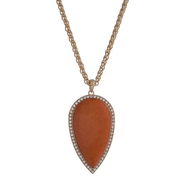 """Gold tone necklace with a 2 1/2"""" orange teardrop shape stone pendant with rhinestone accents. Approximately 32"""" in length."""