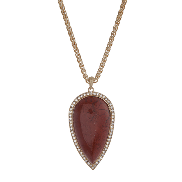 """Gold tone necklace with a 2 1/2"""" clay red teardrop shape stone pendant with rhinestone accents. Approximately 32"""" in length."""