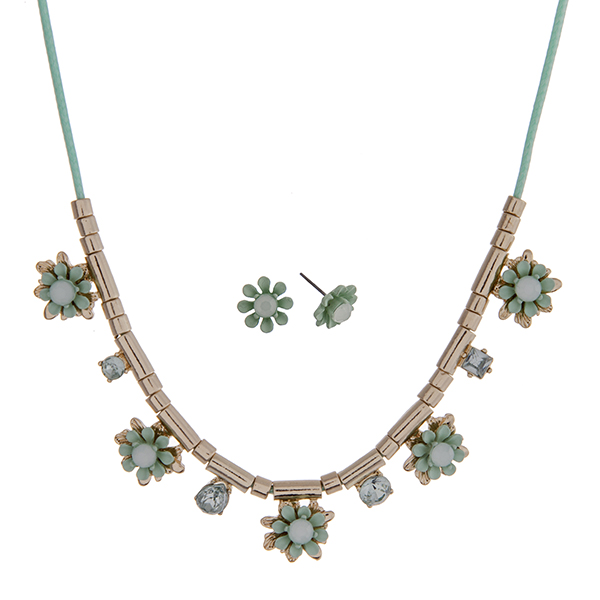 """Mint green cord necklace set with mint green flowers and gold tone beads. Approximately 24"""" in length."""
