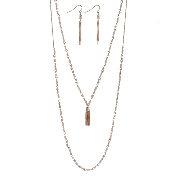 """Dainty gold tone double layer necklace set with ivory beads accented with a chain tassel. Approximately 26"""" in length."""