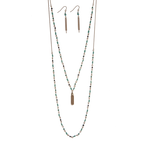 "Dainty gold tone double layer necklace set with turquoise beads accented with a chain tassel. Approximately 26"" in length."