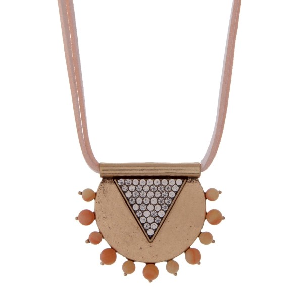 """Pale pink leather necklace featuring a burnished gold tone pendant accented with clear rhinestones and natural colored stones. Approximately 32"""" in length."""
