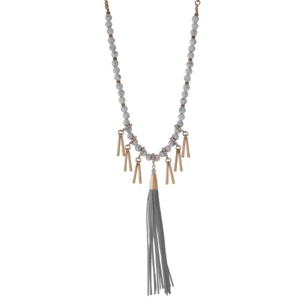 """Burnished gold tone necklace with howlite beads featuring a gray tassel and accented with metal fringe. Approximately 32"""" in length."""