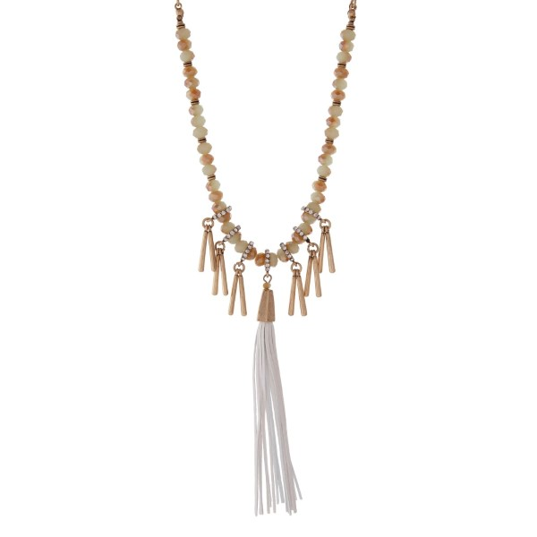 """Burnished gold tone necklace with mint green beads featuring a white tassel and accented with metal fringe. Approximately 32"""" in length."""