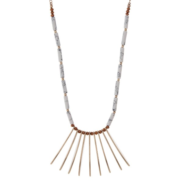 """Gold tone necklace featuring metal fringe, accented with howlite and brown beads. Approximately 32"""" in length."""