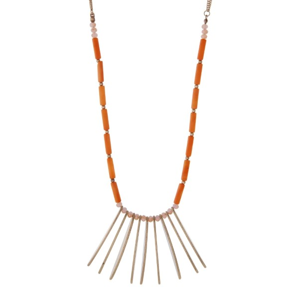 """Gold tone necklace featuring metal fringe, accented with champagne and orange colored beads. Approximately 32"""" in length."""