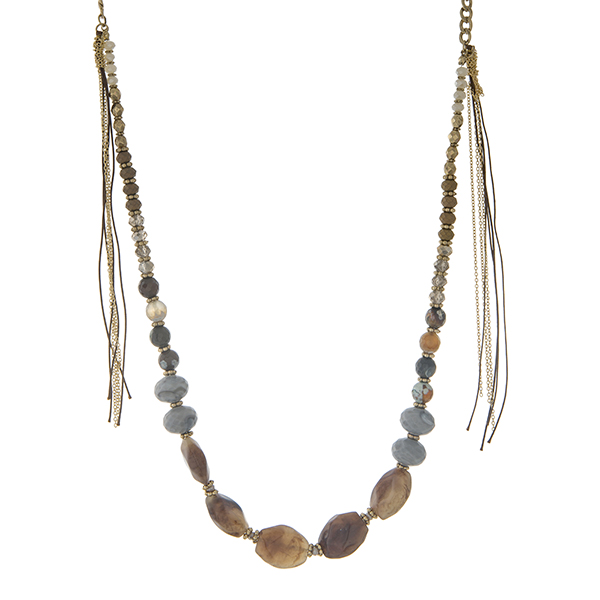 """Gold tone necklace with ivory, gray, and neutral colored beads and two metal tassel. Approximately 32"""" in length."""
