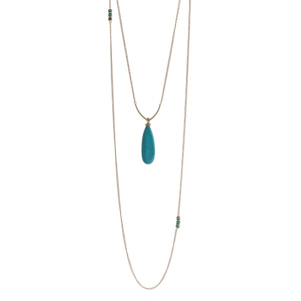 "Gold tone double layer necklace with a turquoise teardrop pendant accented with turquoise glass beads. Approximately 32"" in length."