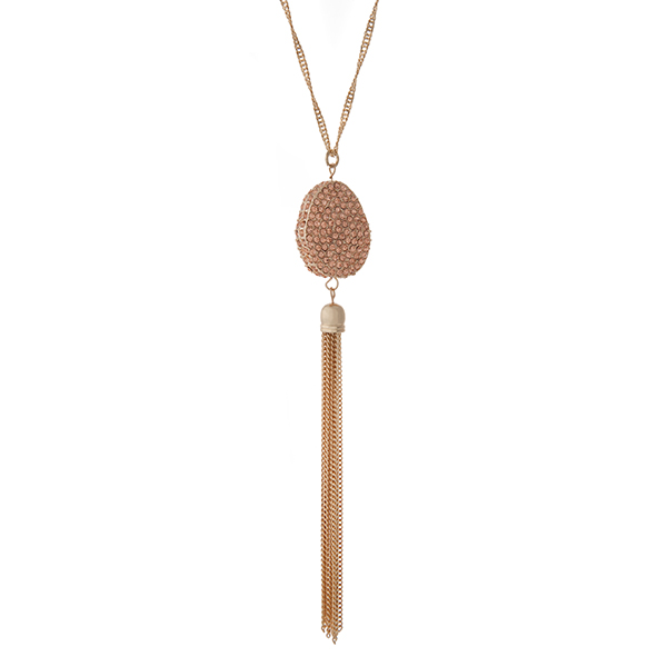 """Gold tone necklace with a peach pave rhinestone pendant and metal tassel. Approximately 36"""" in length."""