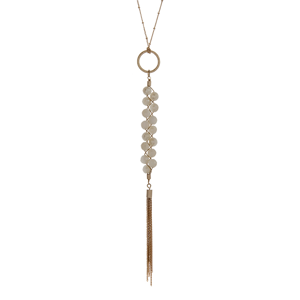 """Gold tone necklace with a braided ivory beaded pendant and a chain tassel. Approximately 36"""" in length."""