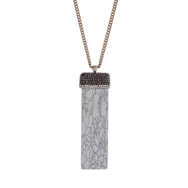 """Gold tone necklace with a rectangle howlite pendant accented with clear and gray rhinestones. Approximately 32"""" in length."""