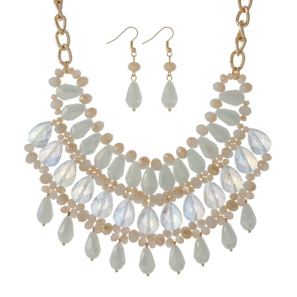 """Gold tone bib necklace set with ivory, white and champagne colored beads. Approximately 18"""" in length."""