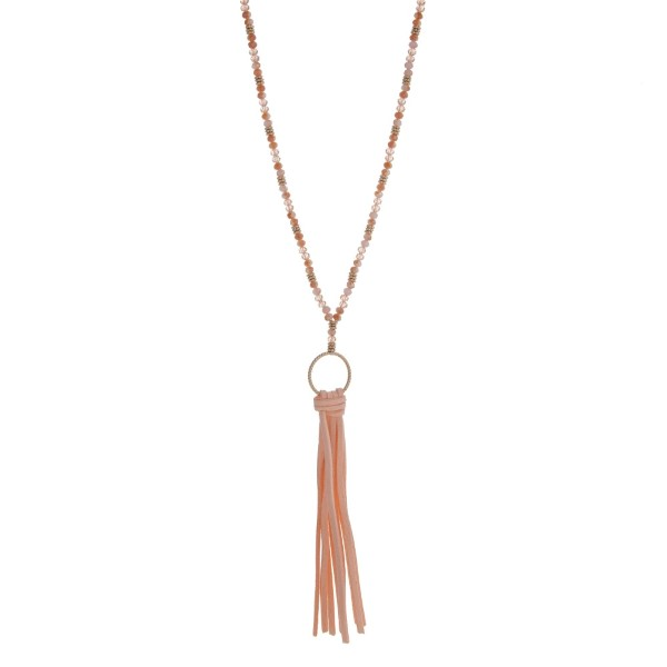 """Gold tone necklace displaying champagne beads with a peach 4 3/4"""" fabric tassel. Approximately 30"""" in length."""