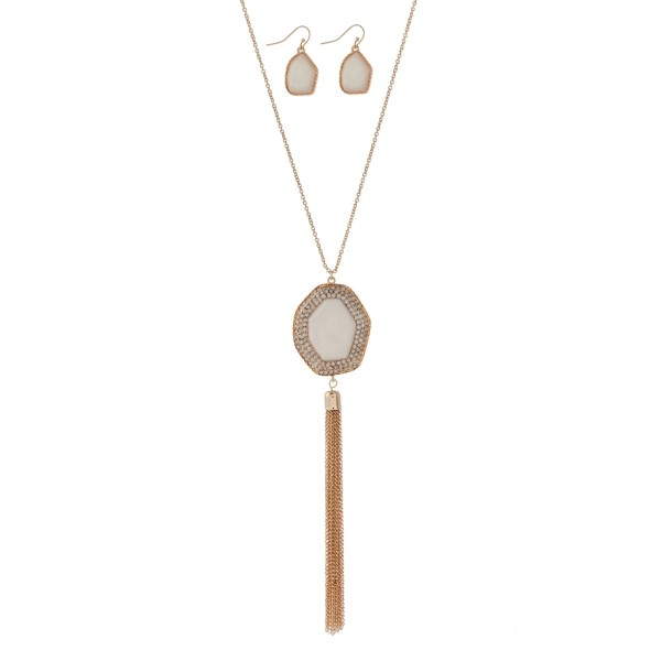 """Gold tone necklace set with an ivory stone pendant surrounded by pave stones and a chain tassel. Approximately 32"""" in length."""