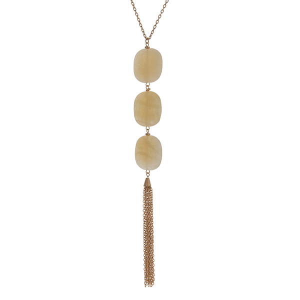 """Gold tone necklace with three beige square natural stones and a metal tassel. Approximately 36"""" in length."""