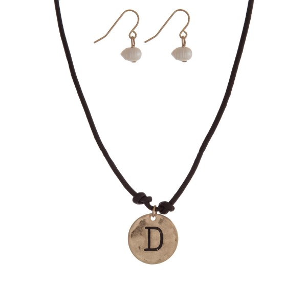 "Brown cord necklace with a gold tone pendant stamped with the letter ""D"" and a pearl closure. Approximately 18"" in length."