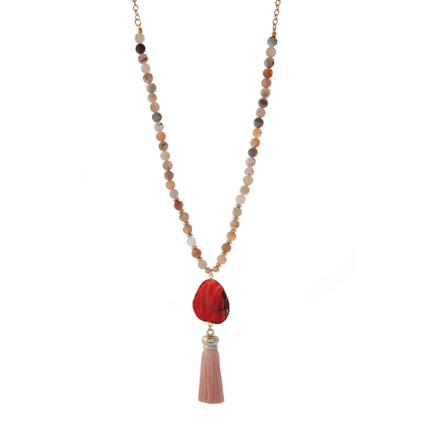 """Gold tone necklace displaying botswana natural stone beads and a peach fabric tassel. Approximately 32"""" in length."""