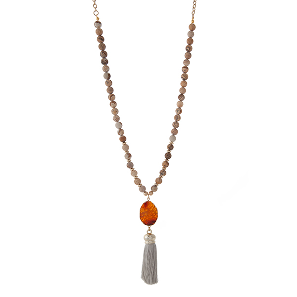 """Gold tone necklace displaying picture jasper natural stone beads and a gray fabric tassel. Approximately 32"""" in length."""