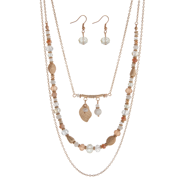 "Gold tone triple layer necklace with champagne beads and a feather charm. Approximately 24"" in length."