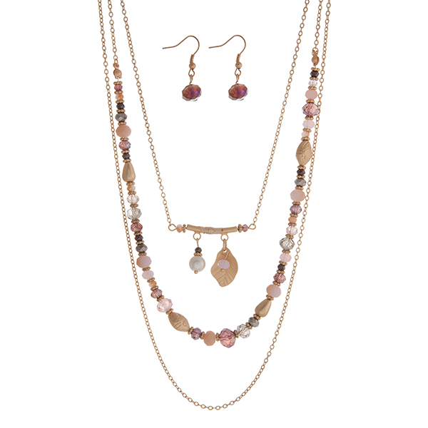 "Gold tone triple layer necklace with pink and purple beads and a feather charm. Approximately 24"" in length."