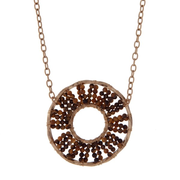 """Gold tone necklace displaying a brown beaded circle pendant. Approximately 32"""" in length."""