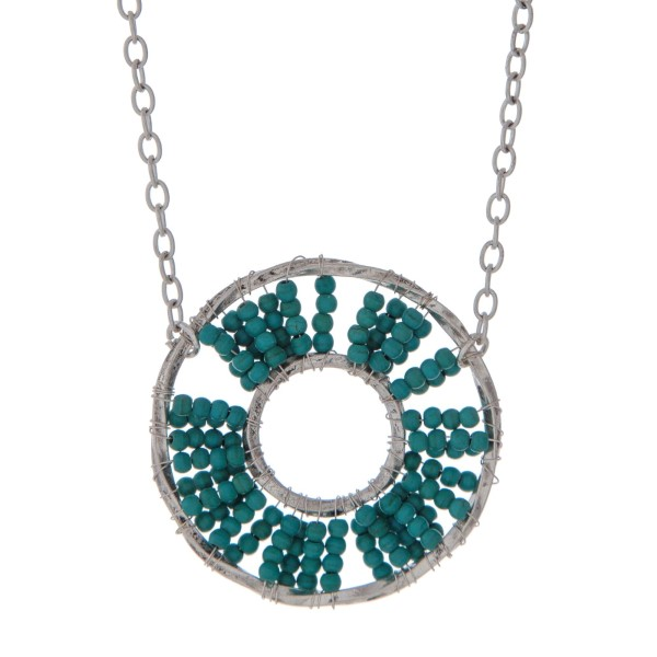 "Silver tone necklace displaying a turquoise beaded circle pendant. Approximately 32"" in length."